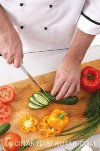 Close-up of male hands cutting cucumber